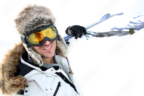 Portrait of swnowboarder standing on snow track