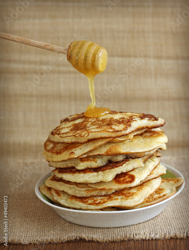 tasty pancakes with honey and wooden dipper on canvas background