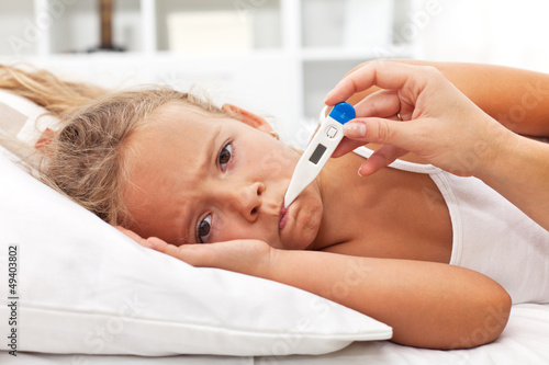 Sick little girl with thermometer laying in bed