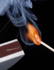 Encendiendo un cerillo,fósforo encendido en fondo negro.