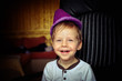 little boy in a purple hat and a white jacket fun grimacing