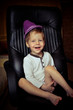 little boy in a purple hat and barefoot fun sitting on a chair