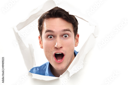 Shocked man looking through paper hole