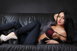 Beautiful brunette lying on a leather couch