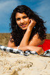 Indian girl with long hair dressed in red on the beach in summer