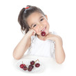 Little girl eating red berries