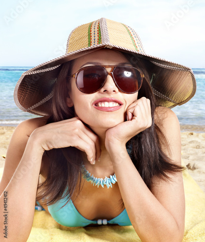 Girl in bikini and hat on beach