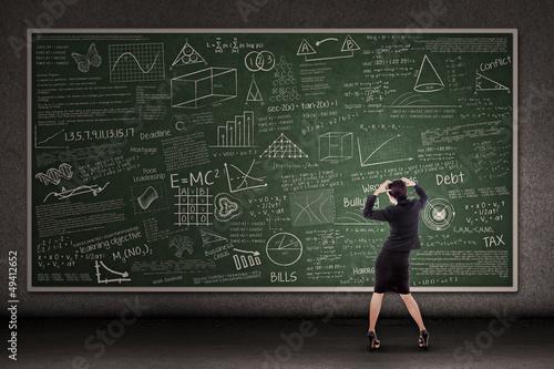 Thinking teacher in front of blackboard