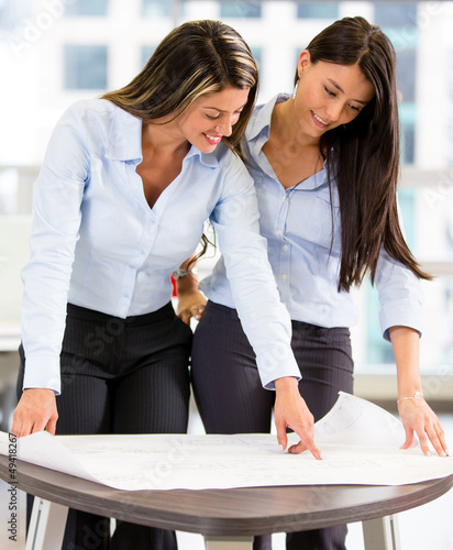 Business women looking at blueprints