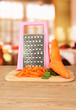 carrots with grater on cutting board on table in kitchen