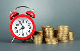 Alarm clock with coins on grey background