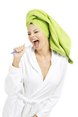 Happy attractive woman singing to tooth brush