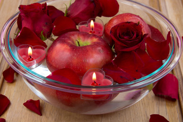 Heart candles in bowl with rose petals and apple