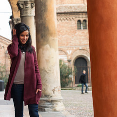 Young woman walking outdoors in s. Stephen, Bologna, Italy.