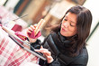 Smiling woman using tablet outdoors while having lunch.