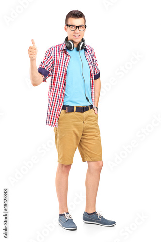 Full length portrait of a young man with headphones giving a thu