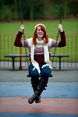 Pretty young female having fun on swing