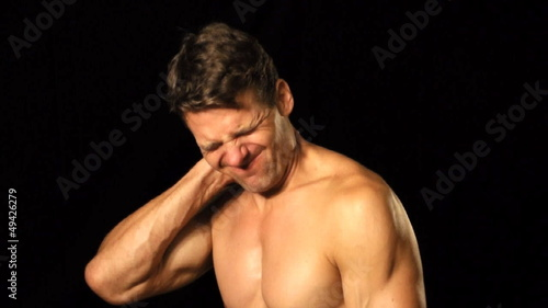 Athletic shirtless man suffers with neck pain