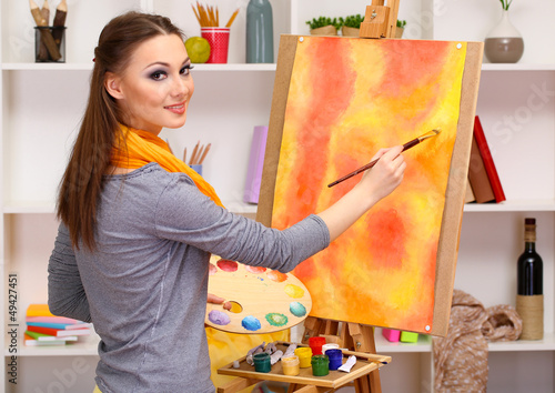 beautiful young woman painter at work,