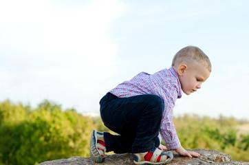 Little boy exploring climbing a rock