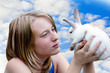 Белый кролик в руках у девушки на фоне неба