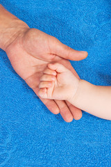 Father is holding babys hand