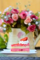 Strawberry cake with flowers on table
