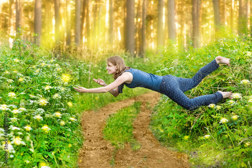 Young woman levitating in the wood