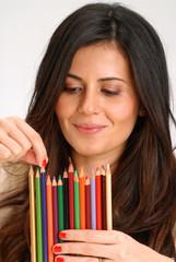 Joven mujer sujetando varios lápices de colores.