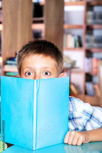 Boy hiding behind book