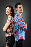 Happy young couple standing back to back over gray background