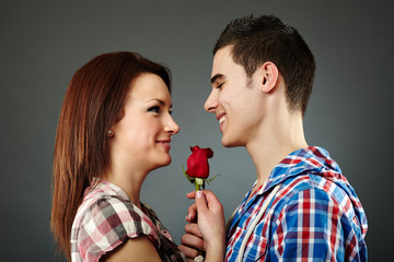 Young man offering a rose to the woman he loves