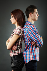 Portrait of sad young couple standing back to back
