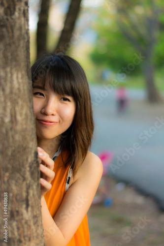 Cute Thai girl hiding behind the tree