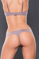 Young woman from the backside in front of grey background