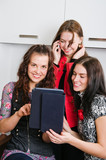 Three women friends chatting at home and using laptop to look at