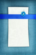 Empty card on blue fabric texture