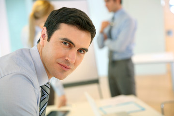 Confident businessman leaning on table