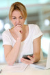 Woman in office looking at smartphone with scary look