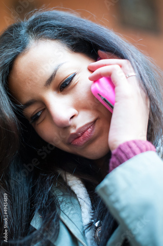 Young girl speaking at mobile phone.