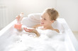 Girl with liquid soap in the bath