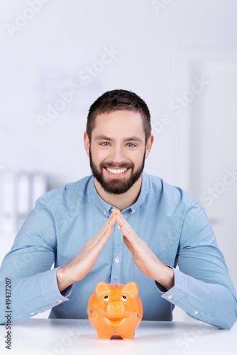 lächelnder mann beschützt sparschwein