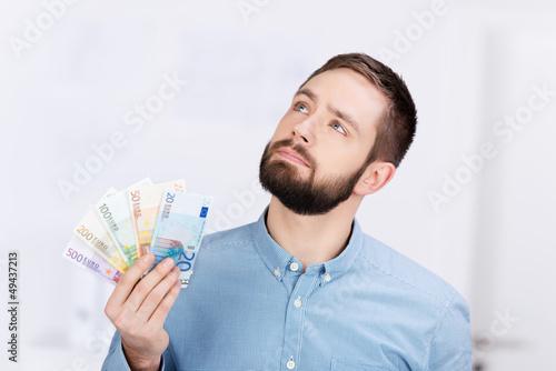 nachdenklicher junger mann mit geldscheinen