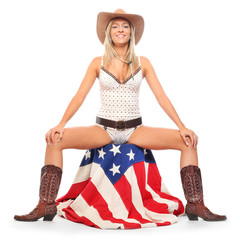 Young cowgirl sitting on a american flag. Feminism concept.
