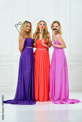 Three women in evening gown with masks.