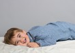 Little boy wearing blue pyjamas in bed