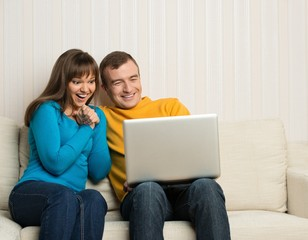 Happy couple sitting on sofa with laptop