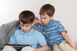 Two brothers playing on tablet