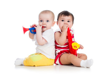 Funny babies girls  with musical toys. Isolated on white backgro