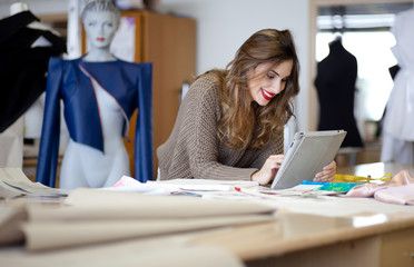 Fashion designer using tablet computer in the studio